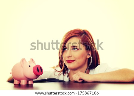 Beautiful, Caucasian nurse listening to a piggy bank with a stethoscope. - stock photo