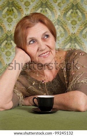 Beautiful Caucasian old woman sitting at a table on a green background