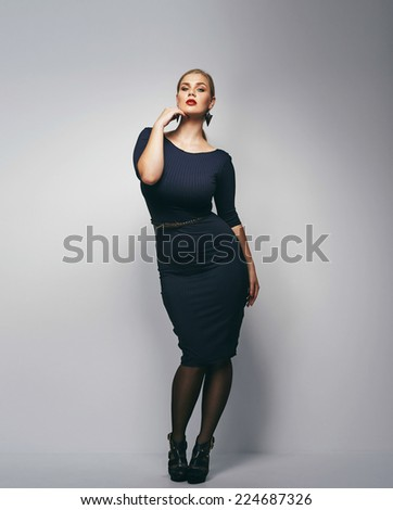 Beautiful caucasian plus size secretary in dark blue dress. Full length portrait of attractive young female posing over grey background. - stock photo