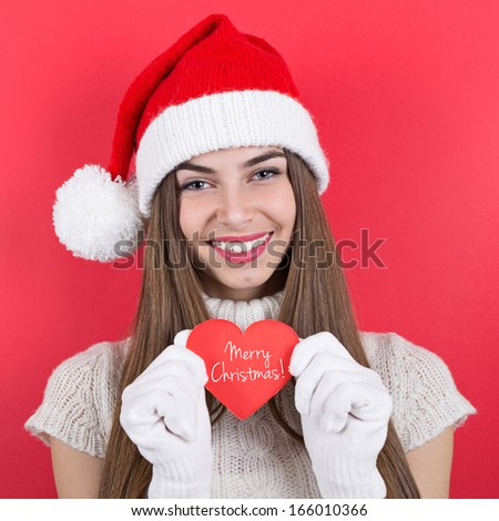 Beautiful Caucasian teenage girl with Santa hat smiling showing red paper heart with Merry Christmas message. Red background. Christmas and holiday concept. - stock photo