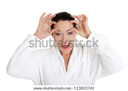 Beautiful caucasian woman checking wrinkles on her forehead, isolated on white background - stock photo