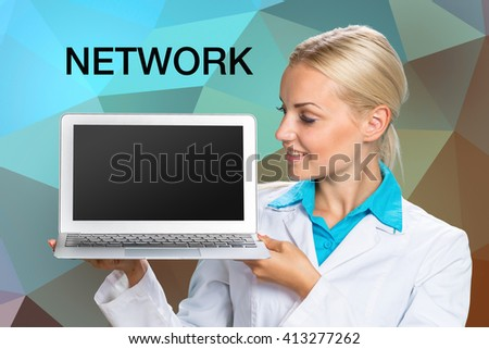 "Beautiful Caucasian woman doctor holding a laptop computer with ""Network"" inscription - stock photo"