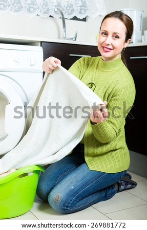 Beautiful caucasian woman doing laundry at home indoors - stock photo