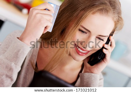 Beautiful caucasian woman doing online shopping with credit card and telephone.
