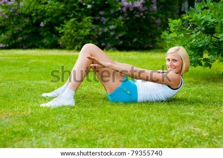 Beautiful caucasian woman doing pilates exercises in the park - stock photo