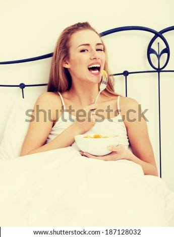Beautiful caucasian woman eating fresh fruit for breakfast in bed. - stock photo