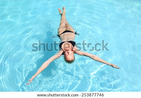 Beautiful Caucasian woman floating in turquoise blue swimming pool. - stock photo