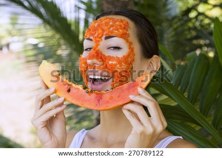 Beautiful caucasian woman having fresh fruit papaya natural facial mask apply, antioxidant skin care and wellness. Facial vitamin mask of papaya slices at spa salon (outdoors). Healthy exotic food - stock photo