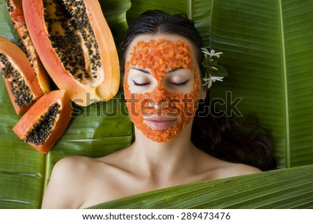 Beautiful caucasian woman having fresh papaya natural facial mask apply, skin care and wellness (outdoors). Facial vitamin mask of papaya slices at spa salon - stock photo