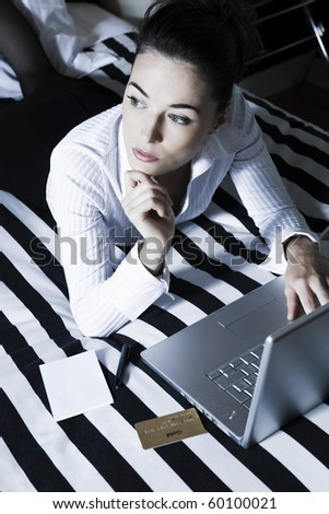 beautiful caucasian woman in a bedroom computing  thoughtful