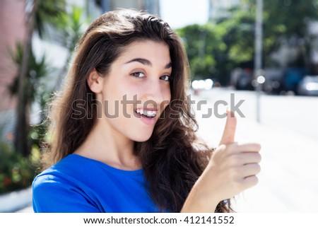Beautiful caucasian woman in a blue shirt showing thumb - stock photo