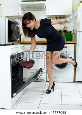 beautiful caucasian woman in a kitchen cooking an heart shape chocolate cake