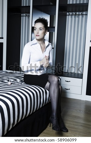 beautiful caucasian woman in bedroom sitting on the bed hand massaging - stock photo