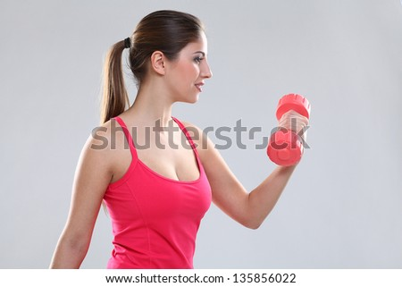 Beautiful caucasian woman in fitness wear with dumbbells over background
