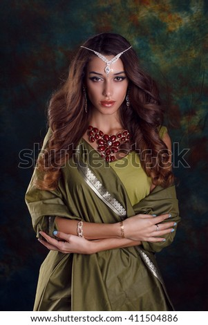 Beautiful caucasian  woman in green indian sari and jewelry on colorful background