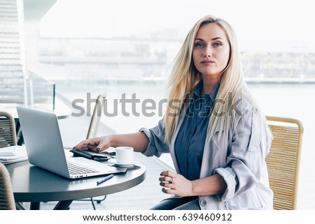 Beautiful caucasian woman is looking at the camera while sitting with a laptop in a modern co-working space. Business woman is working on a portable computer connected to the wi-fi network.