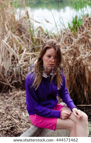 beautiful Caucasian woman model sitting on the lake in nature in the reedsand thinking the wind developing her hair, sportswear, a strong wind developing hair - stock photo
