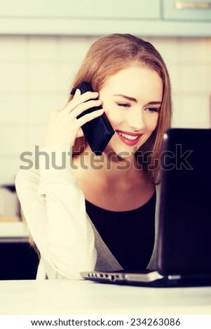 Beautiful caucasian woman talking through phone and working with laptop. Indoor background. - stock photo
