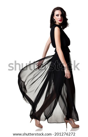 Beautiful caucasian woman wearing black  walking and looking back over her shoulder - stock photo