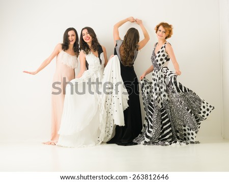 beautiful caucasian women in cocktail dresses posing together, dancing and having fun, against white background - stock photo