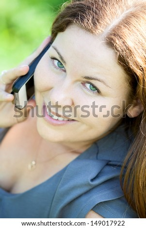 Beautiful Caucasian young woman close-up portrait speaking on phone