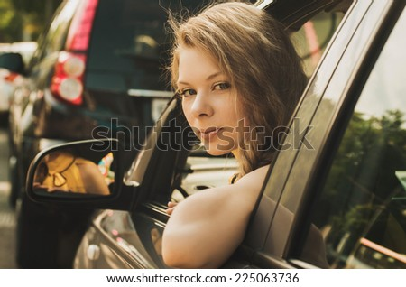 Beautiful caucasian young woman driving a car - stock photo