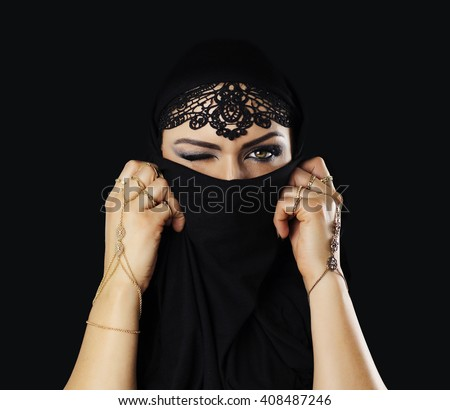 Beautiful caucasian young woman with black veil on face, one eye closed, fancy arabian costume. Isolated on black - stock photo