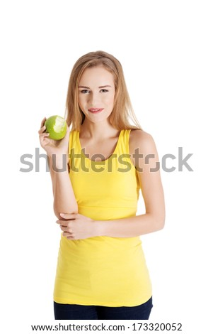 Beautiful causal caucasian woman holding fresh green apple with missing bite. Isolated on white. - stock photo