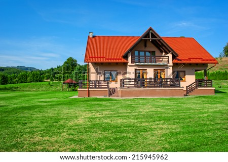 Beautiful chalet surrounded by green grass and blue sky