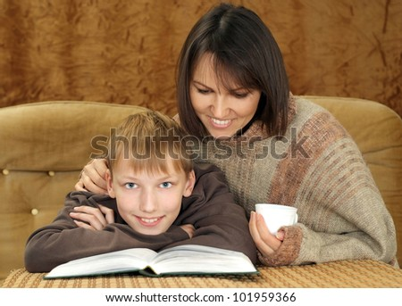 Beautiful charming Caucasian mama with her son reading a book on a brown background