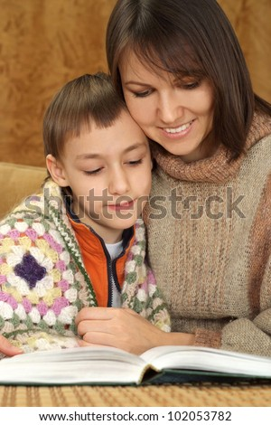 Beautiful charming Caucasian mom with her son on the couch on a brown background