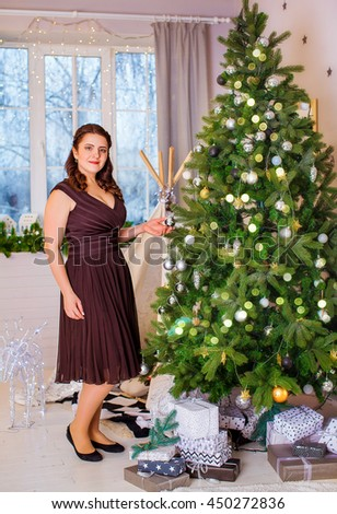 Beautiful charming nice woman in dress standing on the background of Christmas tree. Closeup, Macro, Background - stock photo