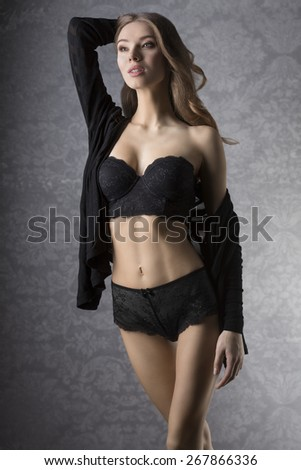 Beautiful, charming, sexy, natural woman with long, curyl, blonde hair in black lingerie and black jumper. She has got nice make up.  - stock photo