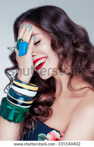 Beautiful charming young caucasian girl with brown chocolate hair, red lips, a lot of bracelets on her hands posing in studio. Happy mood. - stock photo