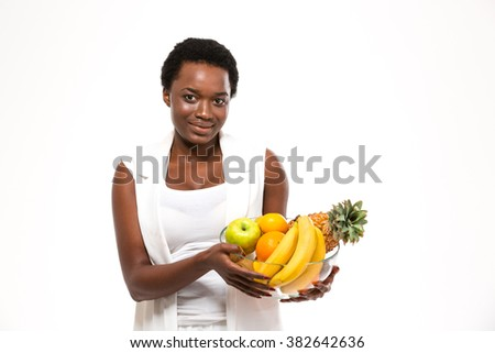 Beautiful cheerful african american young woman standing and holding glass bowl with exotic fruits over white background - stock photo