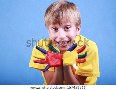 Beautiful cheerful blond boy in a yellow t-shirt showing multicolored painted hands and smiling happily  - stock photo