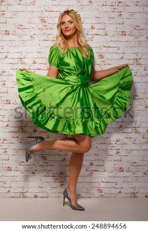 beautiful cheerful blonde in a bright green dress and standing on one leg - stock photo