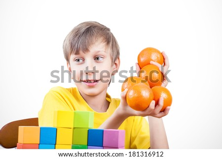 Beautiful cheerful boy in yellow t-shirt holding oranges - stock photo