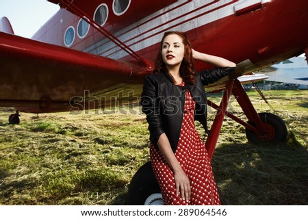 beautiful cheerful brown haired pin-up lady with vintage haircut and red dress and black jacket sits on airplane wheel in setting sun. The airplane is red and vintage and stands on sunlit grass.  - stock photo