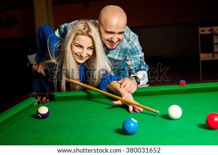 Beautiful cheerful couple plays billiard. Billiard sport concept. American pool billiard. Pool billiard game. - stock photo