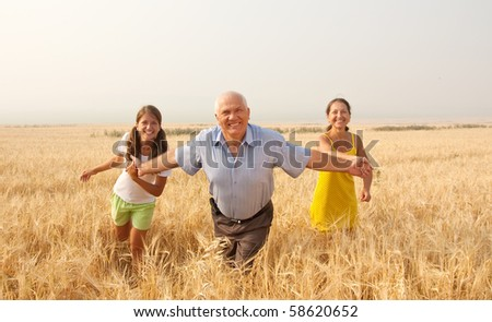 Beautiful cheerful family  runing over a field - stock photo
