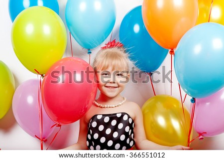 Beautiful cheerful girl holding a lot of colorful balloons