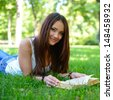 beautiful cheerful girl reading book in the summer park  - stock photo