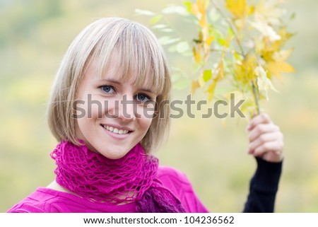 Beautiful cheerful girl with a branch of the autumn foliage. - stock photo