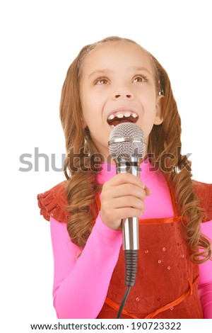 Beautiful cheerful little girl in red dress singing into microphone, isolated on white background.