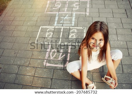 beautiful cheerful little girl playing hopscotch on playground outside  - stock photo