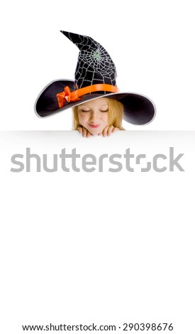 Beautiful cheerful little girl with long blonde hair in the witch costume looking down the sign. Black witch hat with web, spider and orange bow. Copy space. - stock photo