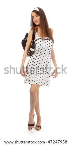 beautiful cheerful model in polka-dot dress with black bag does a slight curtsy - stock photo