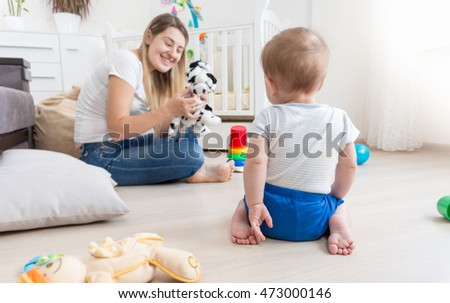 Beautiful cheerful mother playing in puppet show with her baby boy