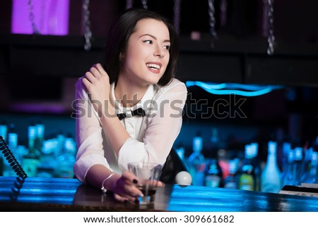 Beautiful cheerful smiling brunette girl in white shirt and black bow tie at nightclub bar, holding glass with drink - stock photo